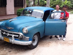 Eddie Moody with a taxi driver and his classic car, one of the pre-1960's vehicles the island is known for.