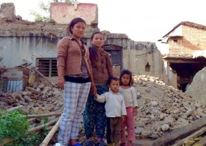 One of the girls in the Empower Nepali Girls program, standing with her family in front of what used to be her home. They are now living in a tent.