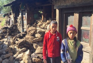 Two Empower Nepali Girls scholarship children stand in front of their damaged house near Lukla in the Mount Everest region of Nepal.