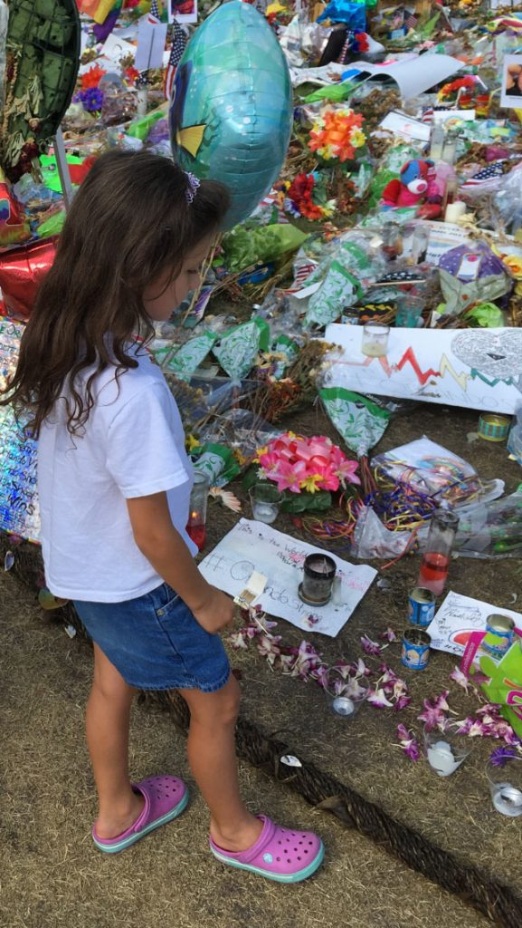 """Lucia Lassiter-Sanabria, the author's 7 year-old daughter, at a memorial site set up recently at the Dr. Phillips Center for the Performing Arts in downtown Orlando. """"I had been talking to Lucia about the [Pulse] shooting and wanted to show the enormous amount of love and support that was given.  It was a tender moment watching her walk around and look at the pictures of the victims and reading some of the signs of love,"""" says Sanabria."""