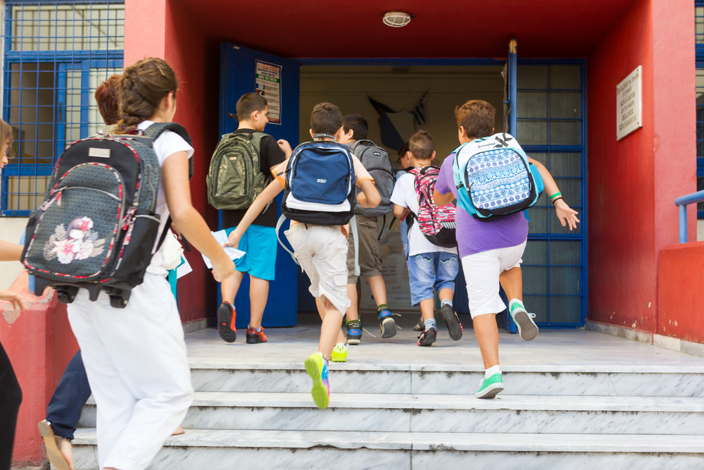Students with their backpacks getting into school. First Day of